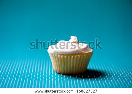 Christmas homemade vanilla cupcake with sweet cream on top against turquoise background - stock photo