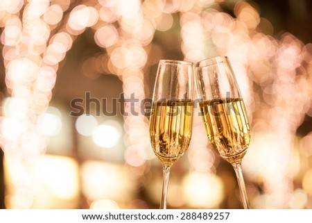 Christmas illuminations and champagne glass - stock photo
