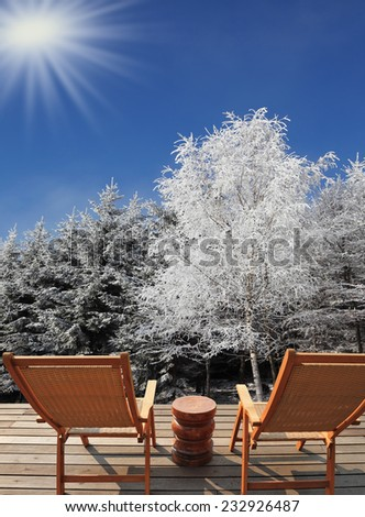 Christmas in the forest. Trees covered with snow. Comfortable wooden chairs and a small round table invite tourists to relax and enjoy the winter wonderland - stock photo