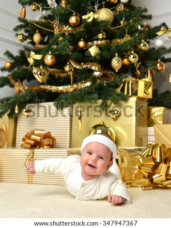Christmas infant baby child lying under christmas tree with gold ball decoration gift presents boxes. New Year 2016 holiday concept  - stock photo