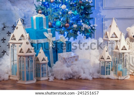 Christmas interior. Beautifully decorated Christmas interior with high blue fur tree surrounded by white lanterns, candles and wrapped presents covered with decorative snow - stock photo