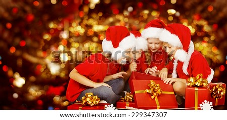 Christmas Kids Opening Present Gift Box, Happy Children in Santa Hat, Smiling Boys and Girls In Red Cap Funny Looking Toys - stock photo
