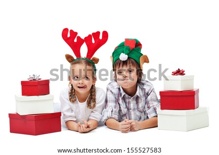 Christmas kids with presents and funny hats making faces - isolated - stock photo