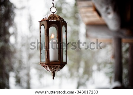 Christmas lantern hanging from porch - stock photo