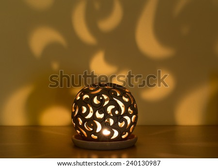 christmas lantern with candle in the darkness and shaddows on wall - stock photo
