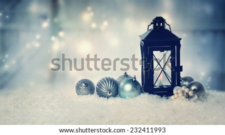 Christmas lantern with ornaments in the snow at night  - stock photo