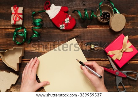 Christmas letter writing on yellow paper on wooden background with decorations - stock photo