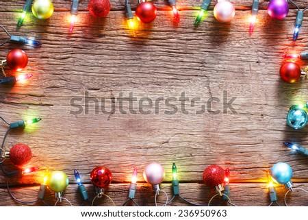 christmas light decorations on wood texture - stock photo