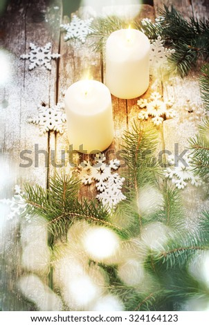 Christmas Light with Bokeh and White Burning Candles with Christmas Decor Snowflakes and Green Fir Tree on Wooden Background. Vintage style - stock photo