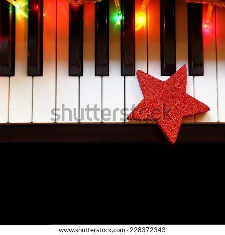 Christmas lights and ornament on piano keys - stock photo