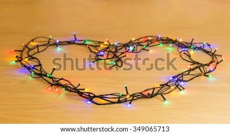 Christmas lights arrange in heart shape on wooden table - stock photo