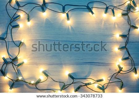 Christmas lights  frame on a wood toned - stock photo