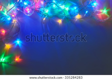 Christmas lights frame on dark blue background with copy space. Decorative garland - stock photo