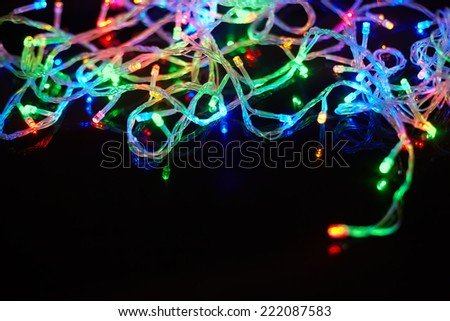 Christmas lights on black background with copy space. Decorative garland - stock photo
