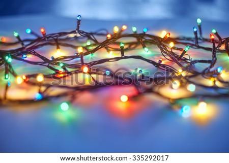 Christmas lights on dark blue background. Decorative garland - stock photo