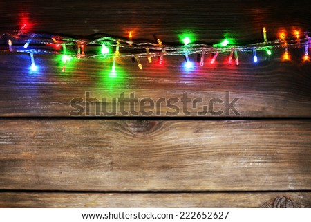 Christmas lights on wooden background - stock photo
