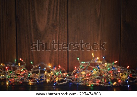 Christmas lights on wooden background. Selective focus - stock photo