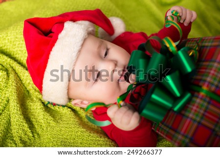 Christmas little baby boy with Santa hat and gift - stock photo