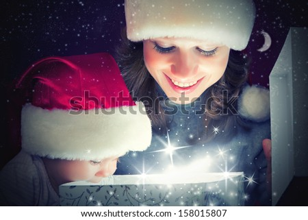 Christmas magic gift box and a woman happy family mother and Child baby - stock photo