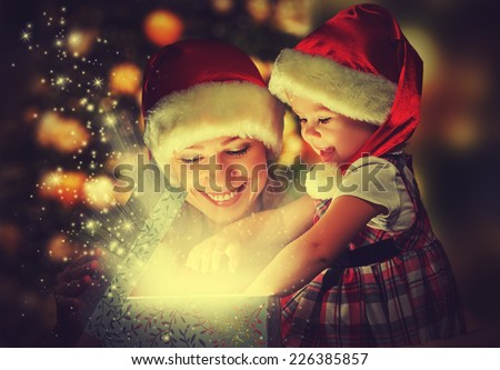 Christmas magic gift box and a woman happy family mother and daughter baby girl - stock photo