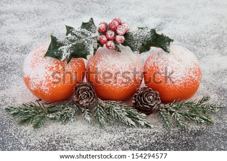 Christmas mandarin orange fruit decoration with snow, holly, fir and pine cones.  - stock photo