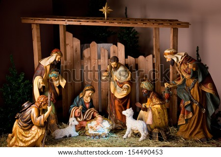 Christmas Manger scene with figurines including Jesus, Mary, Joseph, sheep and magi. - stock photo