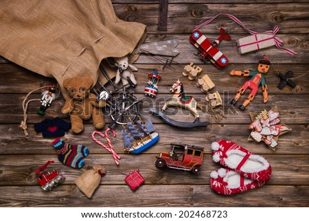 Christmas memories in childhood: old and tin toys on wooden background for gifts. - stock photo