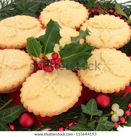 Christmas mince pie group with holly surrounded by ivy and cedar leaf sprigs, mistletoe, red bauble and bead decoration over white background. - stock photo