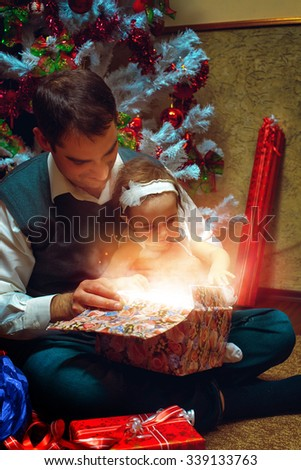 Christmas miracle. Happy father and little daughter opening a present. Christmas mood. New year. - stock photo