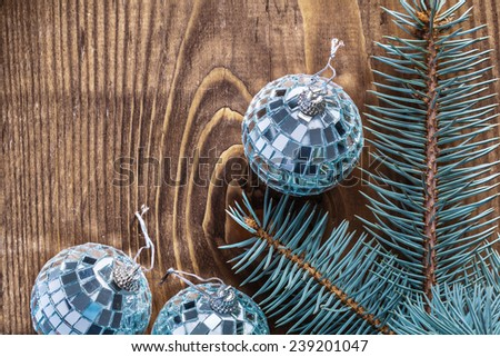 christmas mirror disco balls and branch of pinetree on old wooden board with copyspace - stock photo