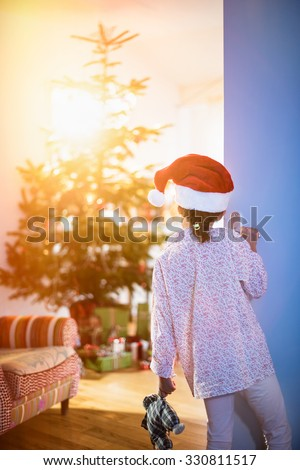 Christmas morning, a little girl in pajamas, wearing a Santa Claus hat opens the living room door and discovers the Christmas tree and many gift.The sun coming through the window gives cozy atmosphere - stock photo