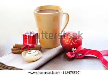 Christmas morning and new year. Cup of hot chocolate with cinnamon sticks, candy, Christmas ball and small box present on wooden table - stock photo