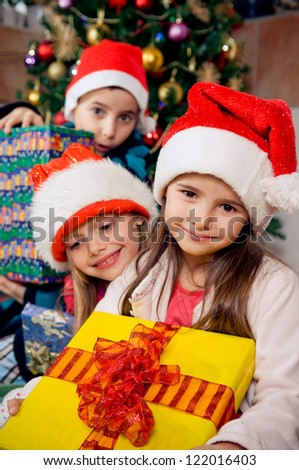 Christmas morning. Happy kids in pajamas holding their christmas gifts. - stock photo