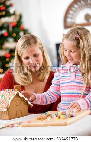 Christmas: Mother And Girl Decorating Gingerbread House Together - stock photo