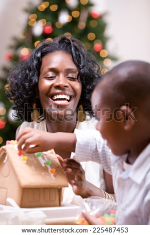 Christmas: Mother Laughs While Child Works On Gingerbread House - stock photo