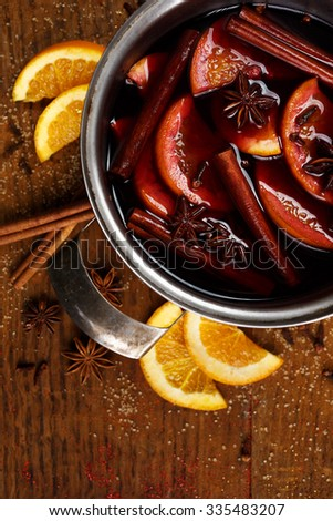 Christmas mulled red wine with addition cinnamon sticks, anise stars, cloves, oranges and brown sugar  in a pot  on a rustic wooden table - stock photo