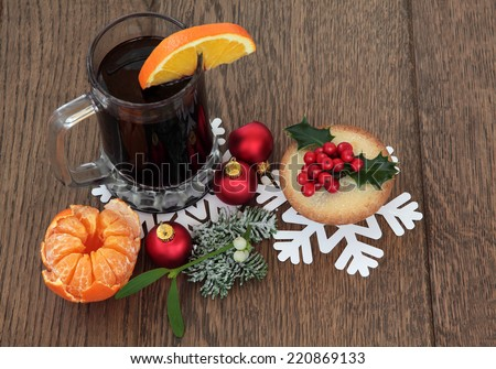 Christmas mulled wine with mince pie, red bauble decorations and winter flora over oak background. - stock photo