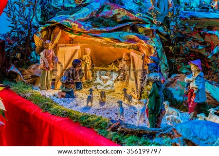 Christmas Nativity scene, Blessed Virgin Mary and Saint Joseph watch over the Holy Child Jesus as the ox and the donkey are warming while the three wise men bring gifts of gold, frankincense and myrrh - stock photo