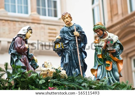 Christmas nativity scene with three Wise Men presenting gifts to baby Jesus, Mary & Joseph. Christmas market in Germany. - stock photo