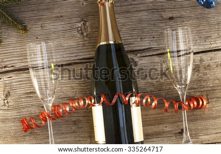 Christmas, New Year, Celebration, Champagne in a glass bottle, two glasses of wine, tree, bells, streamers, Top view, closeup. - stock photo
