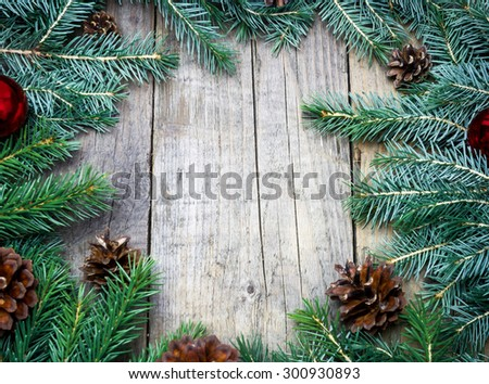 Christmas (New Year) decoration composition. Top view of fur-tree branches and cones frame on wooden background with place for your text - stock photo