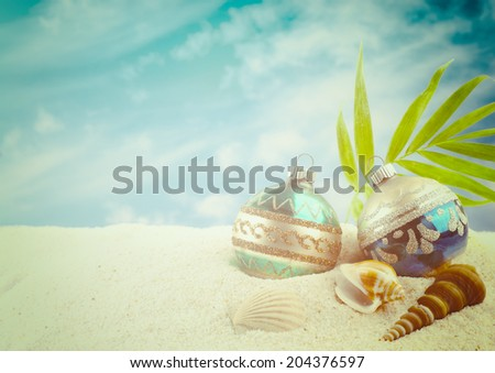 Christmas on the Beach with Two Vintage Ornaments, Sea Shells, palm fronds against background of white sand and blue sky with clouds.  Horizontal with room or space for copy, text, words. - stock photo