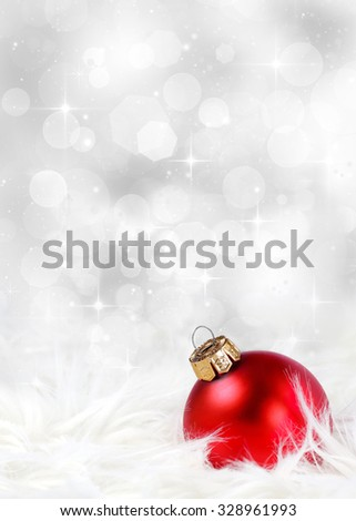 Christmas or holiday background with a red ornament against a festive, sparkling silver background  - stock photo