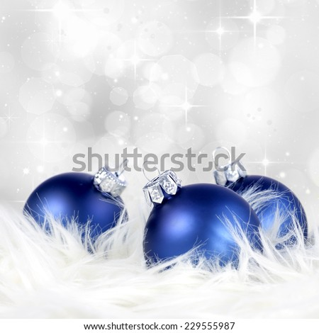 Christmas or holiday background with blue and silver ornaments on billowy feathers  - stock photo