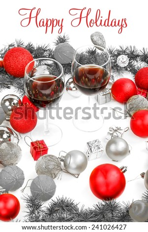Christmas or New Year decoration with pine or fir and red ornaments balls with two glasses of wine.  Happy Holidays text greeting card. Black and White photo with separate red color - stock photo