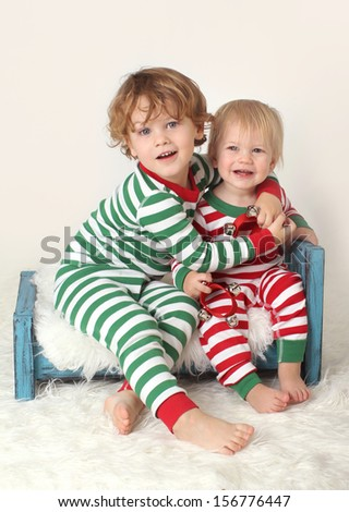 Christmas or winter themed image, children with striped pjs on bed with jingle bells - stock photo