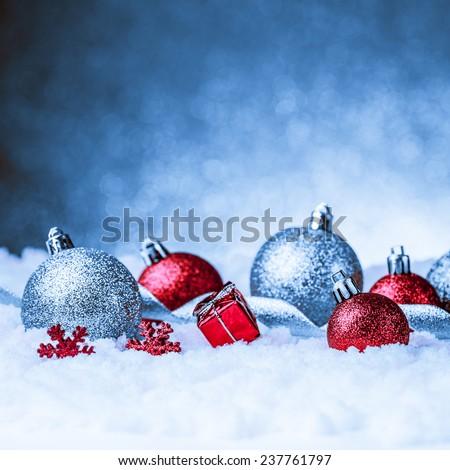 christmas ornament in snow on glitter background. studio shot - stock photo