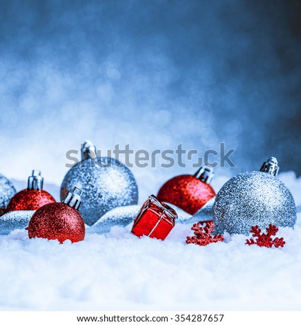 christmas ornament in snow on glitter background. studio shot - stock photo