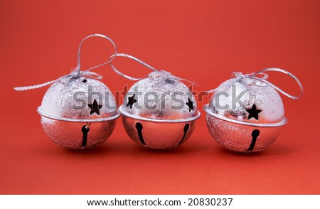 Christmas ornament - three  jingle bells on red. - stock photo