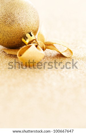 christmas ornament with ribbon on gold with copy space - stock photo